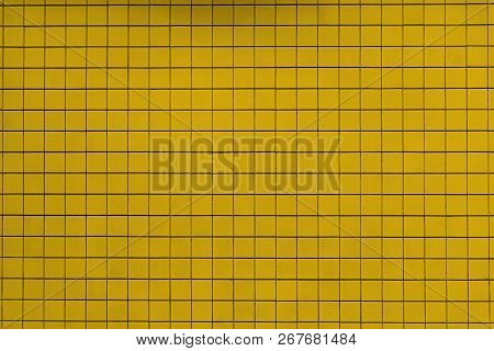 Close-up Of A Yellow Colored Tiled Wall Background Or Texture.  Geometric Shapes And Backgrounds.