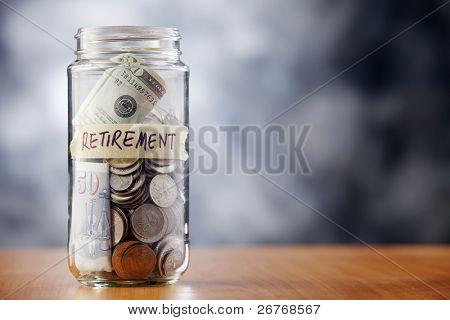 ein Glas von Geld auf den Tisch.