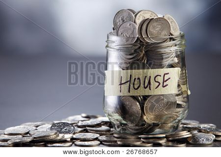Glass jar labeled house filled with coins.