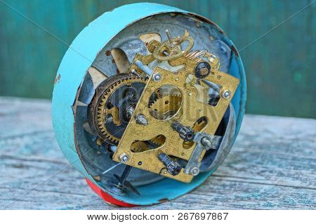Big Old Clock Alarm Clock With An Open Mechanism On A Gray Table