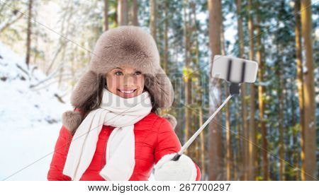 people, technology and leisure concept - happy woman in fur hat taking picture by smartphone selfie stick over winter forest background