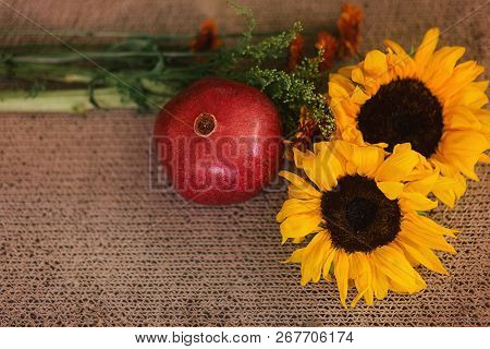 Bouquet Of Sunflowers And A Red Pomegranate On A Tan Textured Background