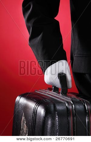 Hotel porter carrying suitcase, close up, side view