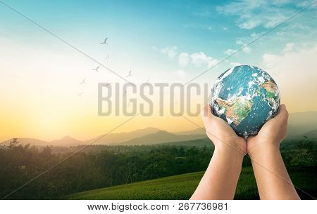 Community Sharing Concept: Human Hands Holding Earth Global Over Mountain Sunrise Background. Elemen