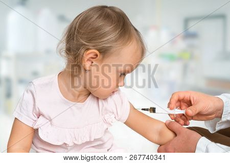 Pediatrician Doctor Is Injecting Vaccine To Shoulder Of Baby - Vaccination Concept
