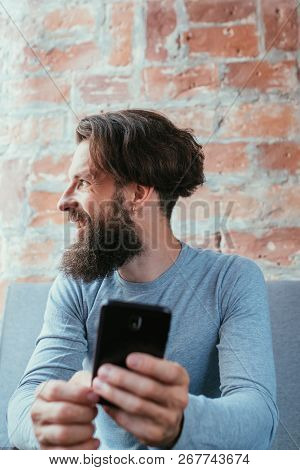 Leisure Lifestyle Relaxation. Smiling Man Holding Phone Looking Sideways