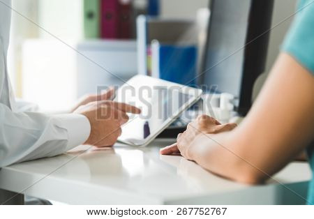 Doctor With Tablet And Patient Having A Discussion, Meeting And Appointment In Hospital Office Room.