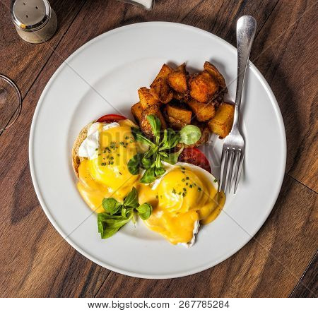 Eggs Benedict Is A Traditional American Breakfast Or Brunch Dish  With Bacon, Ham, A Poached Egg, An