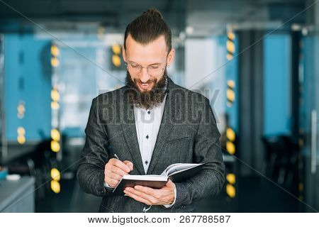 Man Writing Memos In Notebook To Keep Track Of Business Agenda And Timetable.