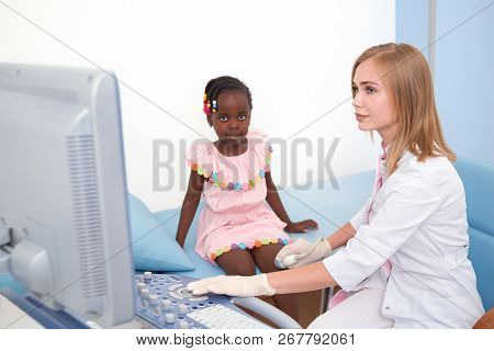 Beautiful Young Female Doctor Doing Ultrasound Of Little Afro Kid Knee Joint With Special Equipment