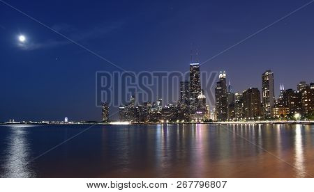 Chicago City Urban Skyscraper At Night At Downtown Lakefront Illuminated With Lake Michigan And Wate