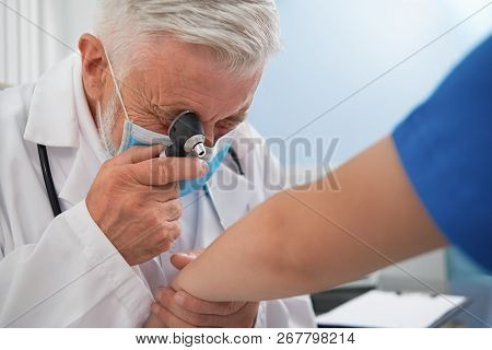 Professional Therapist Holding Special Tool Near Eye For Diagnosis Disease Of Skin. Doctor With Grey