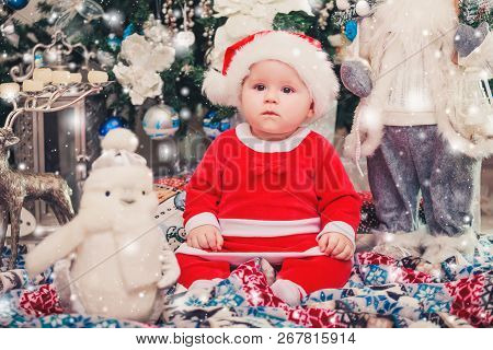 Baby First Christmas. New Year's Holidays. Baby With Santa Hat With Gift. Living Room Decorated By C
