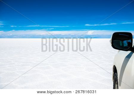Amazing sunshine scenery of bright white Salar de Uyuni in Bolivia with blue sky and white car side view