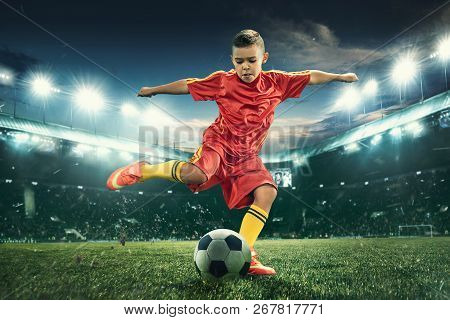 Young Boy With Soccer Ball Doing Flying Kick At Stadium. Football Soccer Players In Motion On Green
