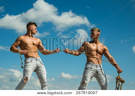 Force And Power. Twins Competitors With Muscular Bodies. Strong Men Pull Rope With Muscular Hand Str
