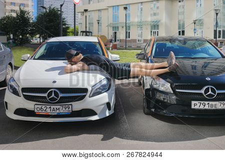 MOSCOW - JUN 20, 2018: Man (with MR) sleeps on two Mercedes Benz cars of Moscow carsharing company You drive, carsharing is system of short-term car rental