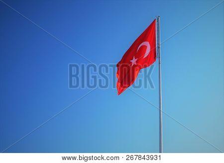 Flag Of Turkey. An Isolated Turkish Flag On A Flag Pole Against A Blue Sky Background