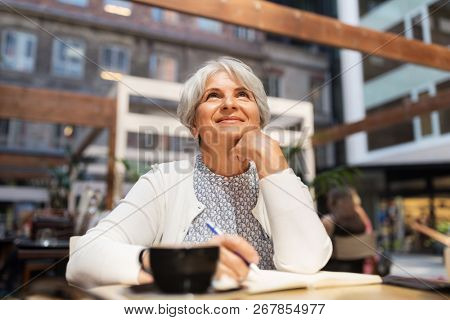 old age, leisure, retirement and people concept - happy senior woman with coffee and notebook dreaming at street cafe