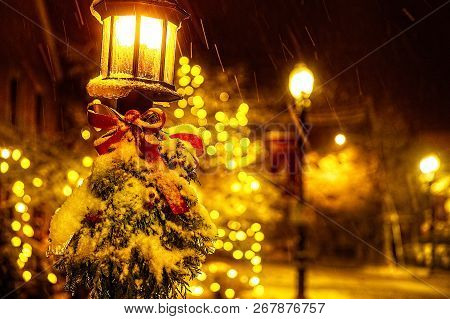 Christmas Tree Branches And A Red Bow On A Lantern Under A Falling Snow. Street Lamp With Christmas