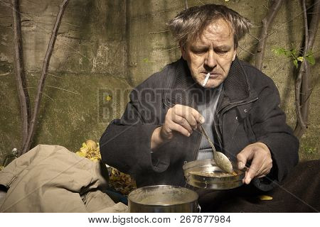 Ugly Pauper Man Living Outdoor Preparing Lentil Soup On Street