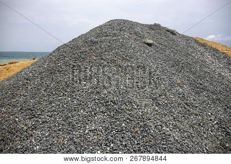 Huge Pile Of Grey Gravel On Coast. Construction Site Material. Big Gravel Heap Outdoor. Construction