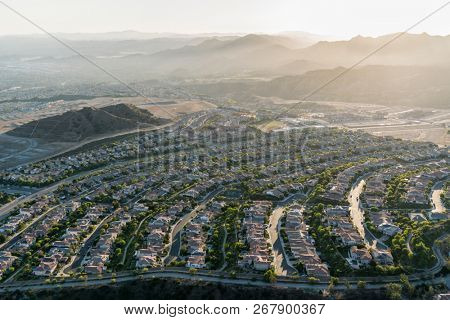 Late afternoon aerial view towards new suburban homes and streets in the sprawling Porter Ranch neighborhood of Los Angeles, California.  The Santa Susana Mountains are in the background.