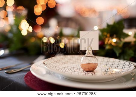 Close up of Christmas table setting with bauble name card holder arranged on a plate and green and red table decorations