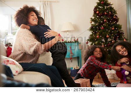 Mother Giving Son Hug As Family Celebrate Christmas At Home Together