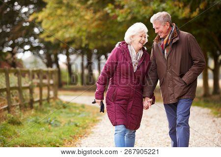 Active Senior Couple On Autumn Walk On Path Through Countryside