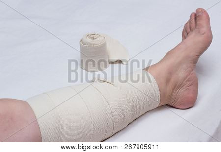 Leg Of An Elderly Woman Bandaged With An Elastic Bandage Against Varicose Veins On The Leg, Close-up