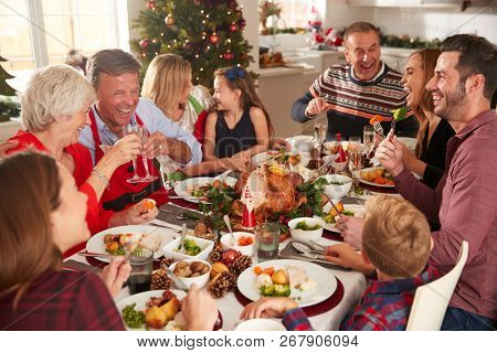 Multi-Generation Family Sitting At Table Enjoying Christmas Meal At Home Together