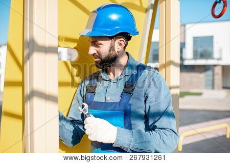 Handsome workman in uniform mounting ladder for kids playing on the playground outdoors poster