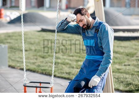 Portrait of a tired workman in uniform on the playground outdoors poster