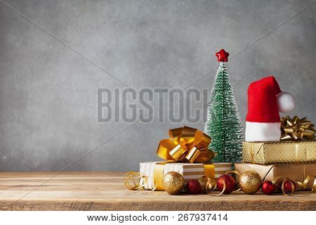 Winter Composition With Christmas Gift Or Present Boxes, Santa Hat And Holiday Decorations On Wooden