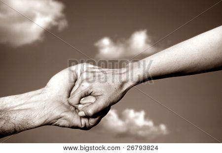 Hände halten und klarer Himmel