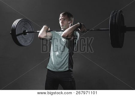 Attractive Male In Sportswear Lifting Heavy Barbell And Looking Away With Serious Face Expression Wh