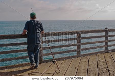 A Man Fishing From A Pier Above The Pacific Ocean In Oceanside, California, Usa