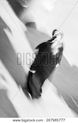 Turkish Woman Is Walking On The Street Where The Sun Sands Soft Shadows To The Ground. Motion Blurr
