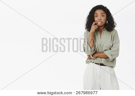 Portrait of anxious cute and feminine dark-skinned female with curly hairstyle clenching teeth from nerves biting finger and staring worried at camera being concerned with troublesome moment poster
