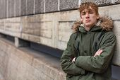 Young adult male teenager boy outside in an urban city wearing a green parka coat leaning against a wall poster