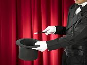 Hands of the magician with magic wand and top hat on stage. poster