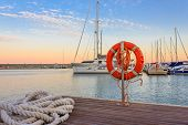 the quay of a marina at  the sunset /a mooring rope with a lifebelt  on  the quay of a marina at  the sunset poster