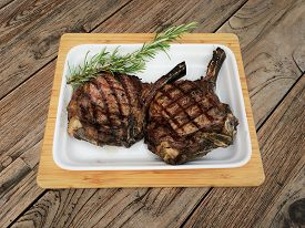 Grilled Veal Chop. A Freshly Grilled Veal Chop On A White Plate With Rustic Wood Table Background.
