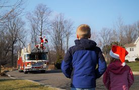 Children Waiting For Santa On A Fire Truck. A Young Boy And Girl Look On As A Firetruck Approaches W