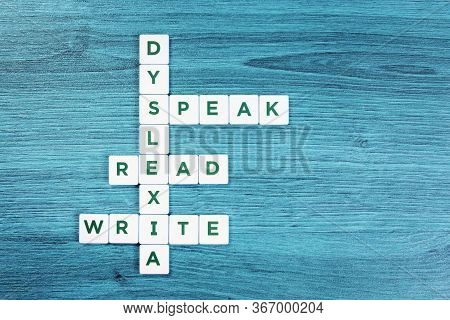 Dyslexia And Read Write Speak Word Cubes On Blue Wooden Desk Background, Reading Difficulty Awarenes