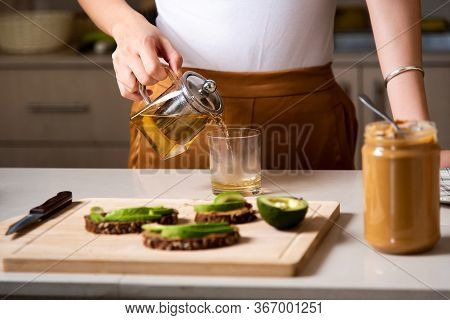 Woman Making Morning Tea To Have With Breakfast At Home
