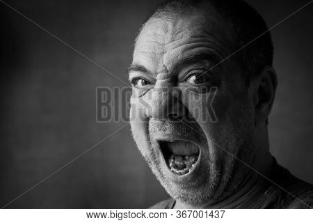 Angry aggressive adult man screaming. Close-up face, black and white portrait