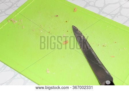 Crumbs Left On The Cutting Board After Slicing Bread And A Knife. Close Up.