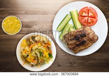Grilled Pork Ribs With Sliced Cucumbers And Tomatoes On A White Plate. Pork Ribs On Brown Wooden Bac